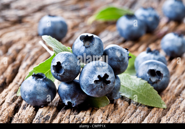 Blueberries with leaves on a old wooden table. - Stock Image