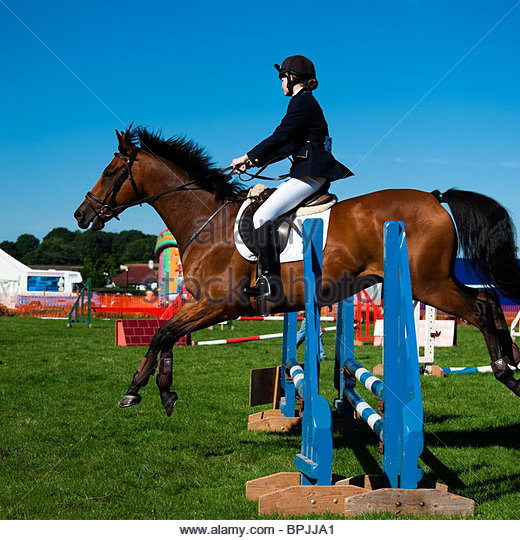 Show jumping competition at Lea Show, Herefordshire, UK. Young woman riding a chestnut horse jumping a fence side - Stock Image