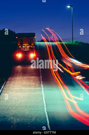 Trucks traveling on road at night  leave streaks of colorful lights - Stock Image