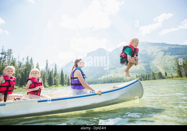Caucasian boy jumping from canoe into lake - Stock Image