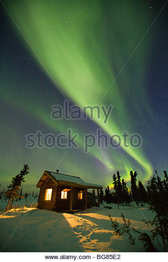 Curtains of green and purple aurora borealis (northern lights) dance over a warm cabin in the hills near Fairbanks, - Stock Image