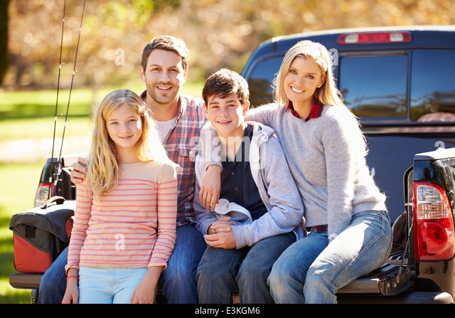 Family Sitting In Pick Up Truck On Camping Holiday - Stock Image