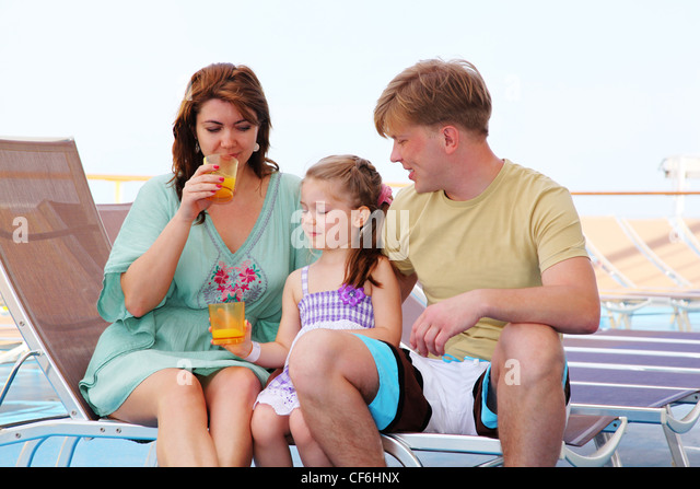 mom dad and daughter rest on deck of yacht and drink tasty juice - Stock-Bilder