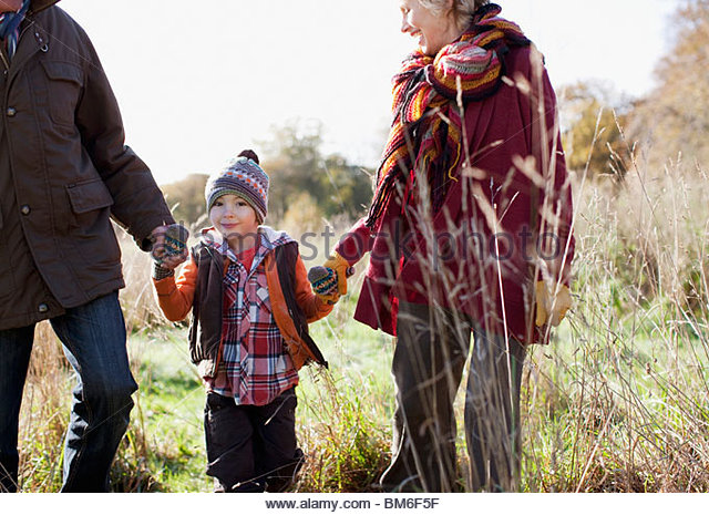 Grandparents holding hands with grandson outdoors - Stock Image