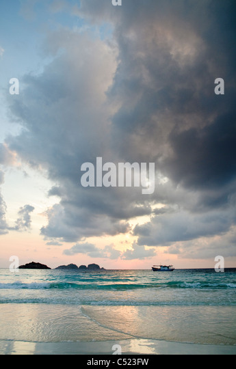 Boat at sunrise with cloud formation, Pulau Redang island, Malaysia, Southeast Asia - Stock Image