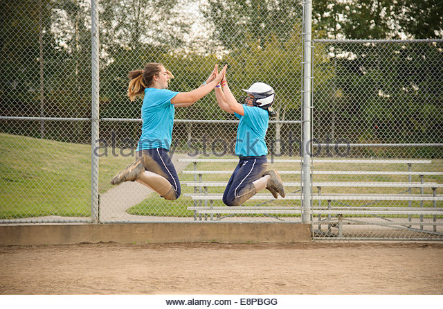 Two girls (10-12) (13-15) jumping and clasping hand - Stock Image