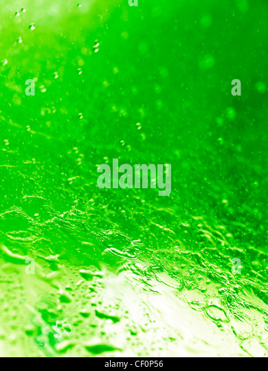 Closeup of splashing water abstract green background texture - Stock Image