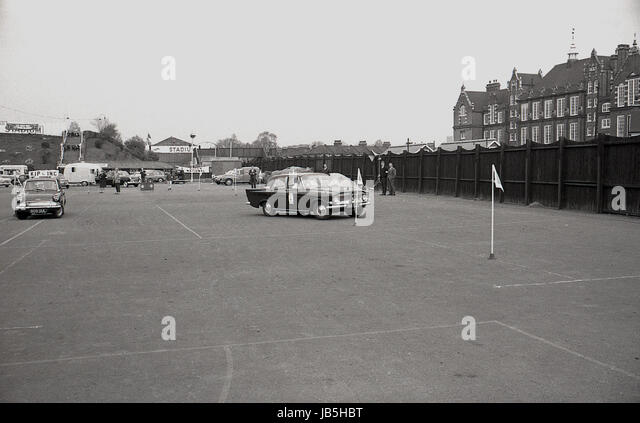 1960s, historical, picture shows cars negotiating around flagposts in the car park at the Catford Greyhound Stadium, - Stock Image