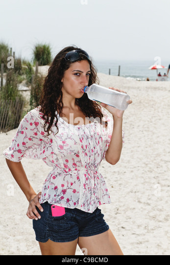 Young Woman Drinking Bottled Water on the Beach, Atlantic City, New Jersey - Stock Image