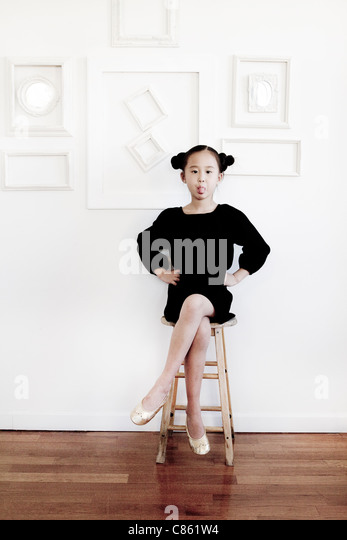 Little girl on stool sticking out her tongue - Stock Image