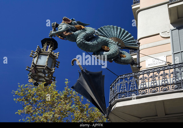 Barcelona Ramblas Art Deco dragon with laterne umbrella shop hanging on a house fassade - Stock Image