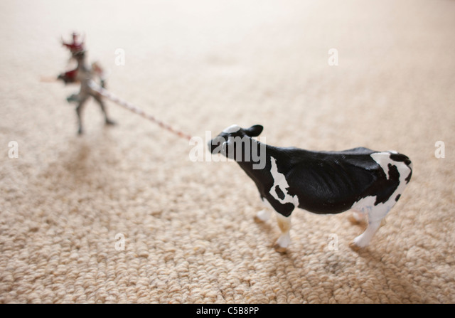 Toy cow and figure on carpet - Stock Image
