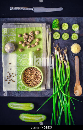 Green vegetables with seasoning on the dark stone background vertical - Stock Image
