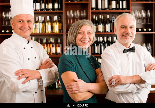 Restaurant manager posing with chef cook and waiter wine bar - Stock Image