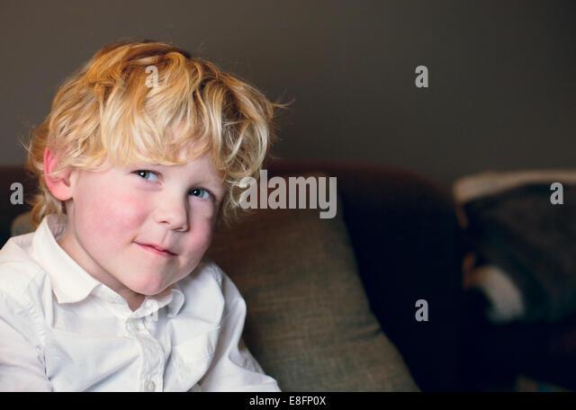 Netherlands, Blonde boy (4-5) in white shirt smiling - Stock Image