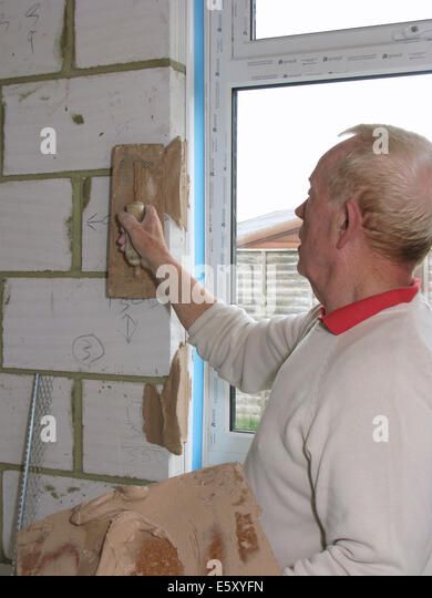 Plasterer fixing corner beading prior to plastering a room in a new property / extension - Stock Image