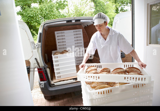 Chef carrying trays of bread to van - Stock Image