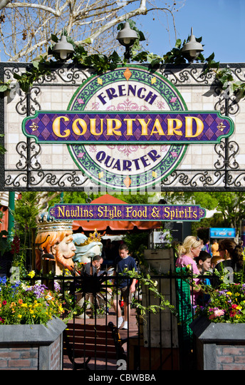 French Quarter Courtyard decorated sign and tourists at Universal Studios Orlando annual Mardi Gras celebration, - Stock Image