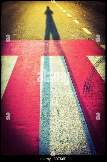 Shadow of an anonymous person on a pedestrian crossing - Stock Image