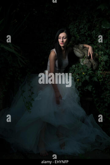 Mid adult woman sitting amongst ivy and rocks - Stock Image