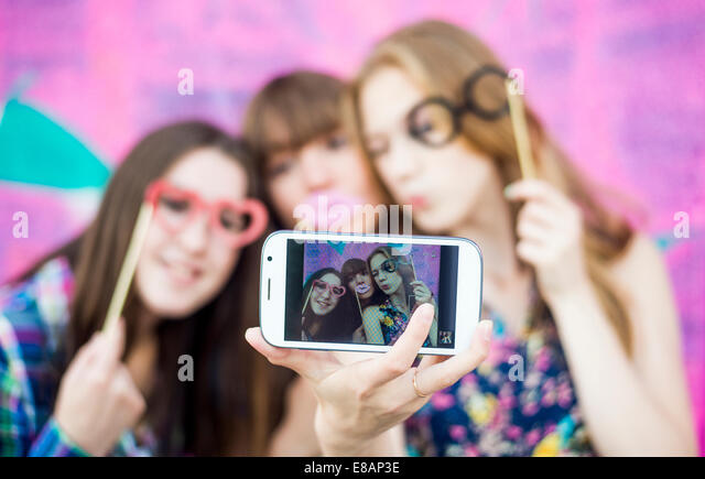 Friends taking selfie wearing fake spectacles and lips - Stock Image