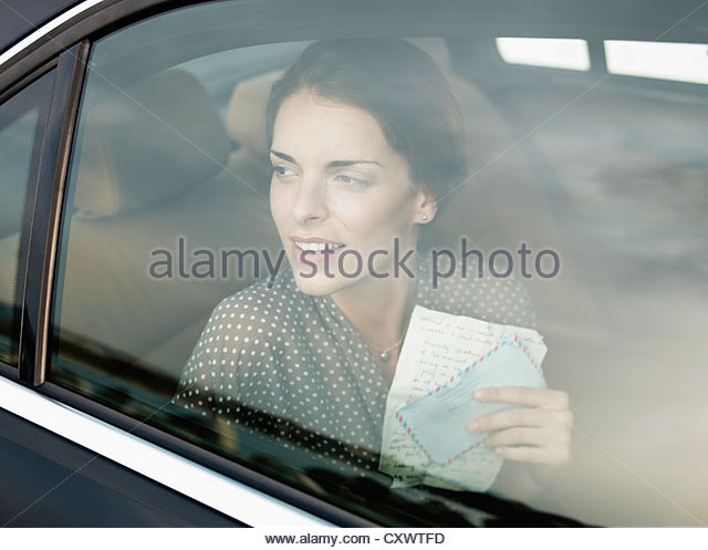 Woman holding letter in backseat of car - Stock Image