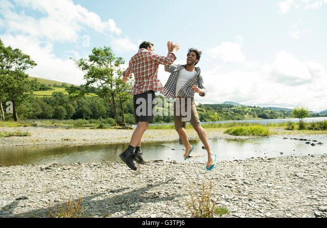 Two men leaping to high five near Bala Lake in Wales. - Stock Image
