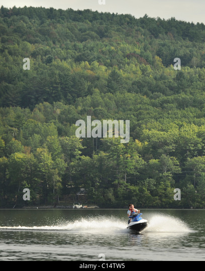 Maine Camp Life : A couple jet skis on Crystal Lake near Harrison, Maine. - Stock Image