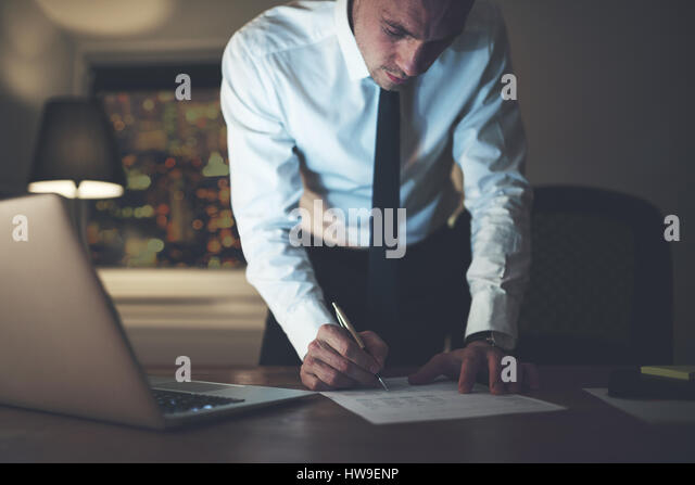 Serious businessman signing contract at office, working at night overtime - Stock Image