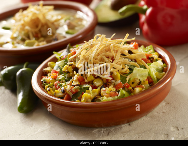 Roasted vegetable salad with lettuce topped with tortilla strips and a bowl of soup - Stock Image