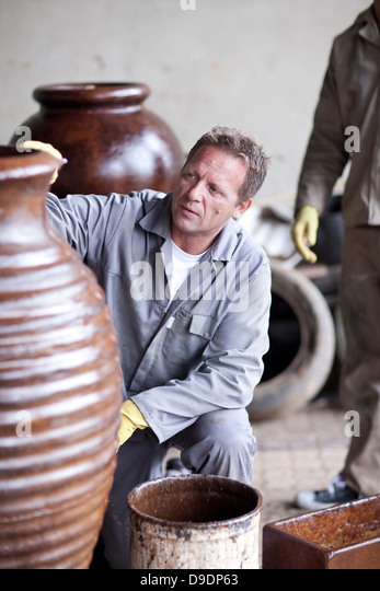 Painting and staining process in pottery factory - Stock Image