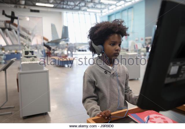 Focused African boy student wearing headphones at interactive exhibit on field trip in war museum - Stock-Bilder