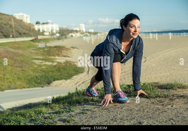 Jogger on her mark by beach - Stock Image