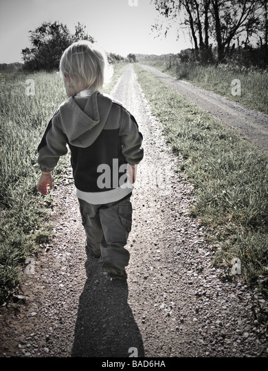 Toddler walking along a gravel road - Stock-Bilder