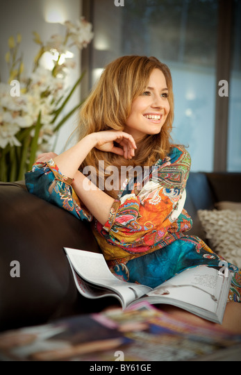 Young woman reads magazine - Stock Image