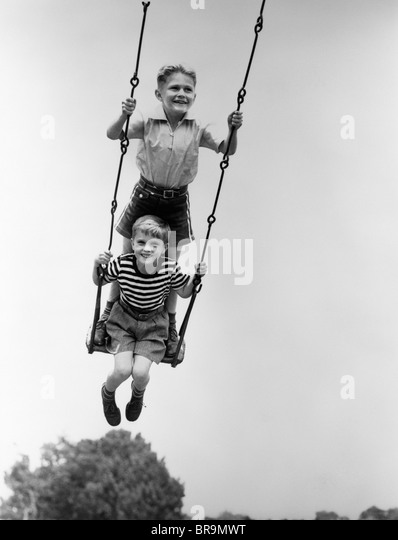 1930s TWO SMILING BOYS SITTING STANDING ON PLAYGROUND SWING - Stock Image