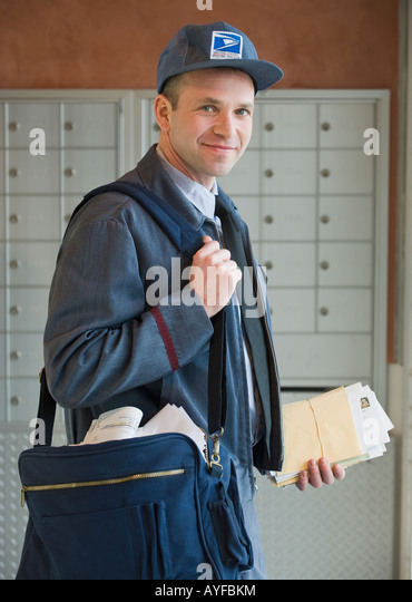 Male postal worker carrying mailbag - Stock Image