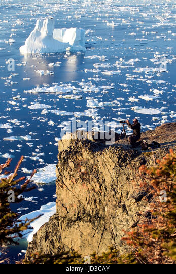 Photographer on cliff in Crow Head, Twillingate, Newfoundland, Canada - Stock Image