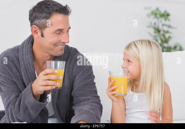 Father and his daughter drinking glass of orange juice - Stock Image