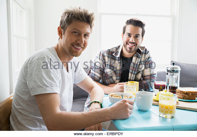 Portrait smiling homosexual couple enjoying breakfast - Stock Image