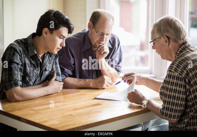 Family discussing over documents at table - Stock-Bilder