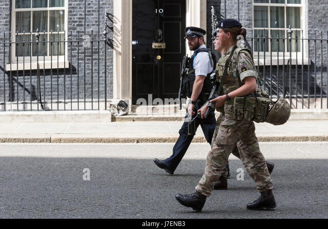 London, UK. 24 May 2017. A police officer and two female soldiers walk past the front door of No. 10 Downing Street, - Stock Image