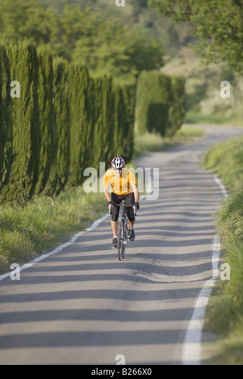 Front view of a man cycling on road - Stock Image