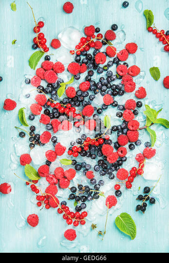 Fresh summer garden berry variety. Rasberry, black and red currant, bilberrry, mint on crushed ice over blue background - Stock Image