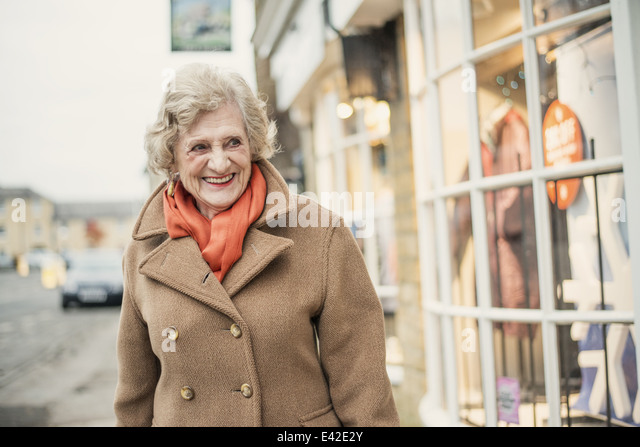 Senior woman walking past shop window - Stock-Bilder