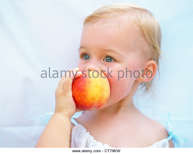 Toddler enjoying peach - Stock Image