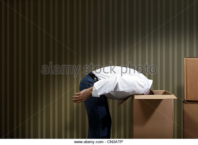Man bending over with head in cardboard box - Stock Image