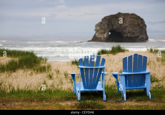 two blue adirondack chairs on a grassy beach with rock formations in the ocean; rockaway beach oregon united states - Stock Image