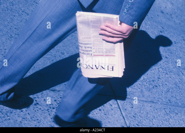 Adult Businessman Walking With a Financial Newspaper Shadow of Man on Pavement New York City USA - Stock Image