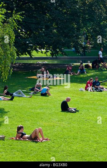 Menschen auf Wiese, Burggarten, Wien, Österreich | people on grass in Burggarten, Hofburg, Vienna, Austria - Stock Image